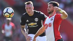 Bek Manchester United, Phil Jones, berebut bola dengan striker Southampton, Shane Long, pada laga Premier League di Stadion St Mary's, Sabtu (23/9/2017). Manchester United menang 1-0 atas Southampton. (AFP/Glyn Kirk)