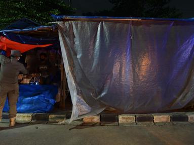 Petugas Satpol PP menertibkan pedagang kaki lima (PKL) di Kanal Banjir Timur, Jakarta, Kamis (28/5/2020). Petugas gabungan menertibkan ratusan lapak PKL karena buka pada masa Pembatasan Sosial Berskala Besar (PSBB) untuk menekan angka penyebaran COVID-19 di DKI Jakarta. (merdeka.com/Imam Buhori)