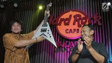 Pemenang lelang diwakili Eddy Gun (kiri) menerima gitar milik band Megadeth yang dilelang dalam acara di Jakarta, Jumat (30/11). Gitar yang dilelang untuk membantu korban gempa di Palu dan Donggala itu terjual seharga Rp150 juta. (New Fimela/Bambang Eros)