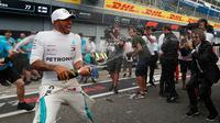 Pembalap Mercedes, Lewis Hamilton menyemprotkan sampanye saat merayakan keberhasilannya memenangkan GP Italia di Sirkuit Monza di Monza, Italia, (2/9). Saat ini Hamilton menempati urutan pertama klasemen dengan 231 poin. (AP Photo/Antonio Calanni)