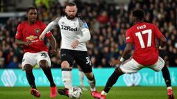 Pemain Derby County Wayne Rooney (tengah) mencoba melewati pemain Manchester United Odion Ighalo (kiri) dan Fred pada pertandingan putaran kelima Piala FA di Pride Park, Derby, Inggris, Kamis (5/3/2020). Manchester United menang dengan skor 3-0. (AP Photo/Rui Vieira)