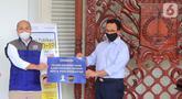 Ketua Umum HIPMI Jaya Afifuddin Suhaeli Kalla secara simbolis menyerahkan bantuan 10.000 masker kain, 5.000 masker medis, APD, sepatu boot dan hand sanitizer kepada Gubernur DKI Jakarta Anies Baswedan di Balaikota Jakarta, Kamis (9/4/2020). (Liputan6.com/Fery Pradolo)