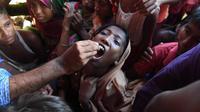 Seorang anak diberi vaksin kolera oleh sukarelawan Bangladesh di kamp pengungsi Thankhali di distrik Ukhia (10/10). Di tengah kekhawatiran wabah, PBB memberikan vaksinasi kolera untuk hampir satu juta orang Rohingya. (AFP Photo/Indranil Mukherjee)