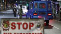 Polisi memeriksa kendaraan saat jam malam diberlakukan untuk mencegah penyebaran COVID-19 di Metro Manila, Filipina, Senin (15/3/2021). Lonjakan kasus COVID-19 di Filipina menambah kekhawatiran atas lambannya vaksinasi dan keengganan publik. (AP Photo/Aaron Favila)