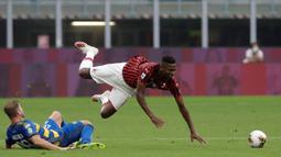 Penyerang AC Milan, Rafael Leao saat dilanggar pemain Parma, Riccardo Gagliolo  pada pertandingan lanjutan Liga Serie A Italia di Stadion San Siro di Milan, Italia (15/7/2020). AC Milan menang telak 3-1 atas Parma. (AP Photo/Luca Bruno)