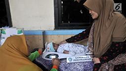 Petugas menimbang bayi saat pemeriksaan rutin kesehatan di Posyandu Ria Balita, Cipinang, Jakarta, Selasa (16/7/2019). Presiden Joko Widodo fokus pada kesehatan ibu hamil dan anak sebagai modal Indonesia menjadi negara maju di masa depan serta mencegah terjadinya stunting. (merdeka.com/IqbalNugroho)