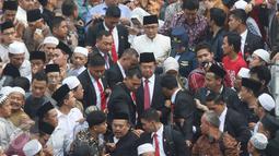 Wapres Jusuf Kalla berada di tengah kerumunan orang saat menghadiri pemakaman Mantan Ketua Umum PBNU KH Hasyim Muzadi di Pondok Pesantren Al Hikam, Depok, Kamis (16/3). (Liputan6.com/Immanuel Antonius)
