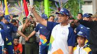 Gubernur DKI Jakarta, Anies Baswedan bersama putranya membawa Api Obor Asian Games 2018 setelah mengelilingi dari Jakarta Timur dan Jakarta Selatan di Balai Kota, Jakarta, Rabu (15/8). (Liputan6.com/Fery Pradolo)