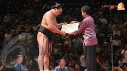 Roy Suryo memberikan penghargaan kepada Harumafuji yang menjadi Juara sejati dalam Kejuaraan Dunia Sumo (Liputan6.com/ Helmi Fithriansyah)