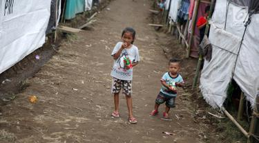 Anak-anak bermain di sekitar tenda Posko Pengungsi Rendang, Bali, Sabtu (2/12). Erupsi Gunung Agung membuat anak-anak tersebut terpaksa harus bermain di posko pengungsian dengan kondisi yang seadanya. (Liputan6.com/Immanuel Antonius)