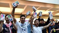 Pelanggan pertama menunjukkan iPhone X setelah ia membelinya di showroom Apple di Sydney, Australia (3/11). Apple iPhone X mulai dijual di Australia dengan antrian panjang di luar toko Apple. (AFP Photo/Saeed Khan)