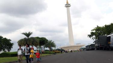 Warga berjalan-jalan di kawasan Monumen Nasional, Jakarta, Jumat (19/4). Libur panjang perayaan Paskah 2019 dimanfaatkan warga untuk berwisata di kawasan Monumen Nasional. (Liputan6.com/Helmi Fithriansyah)