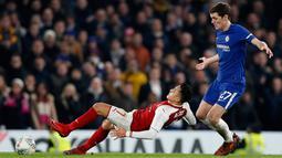 Pemain Arsenal Alexis Sanchez terjatuh di depan pemain Chelsea Andreas Christensen saat berebut bola pada laga semifinal pertama Piala Liga Inggris di Stadion Stamford Bridge, Rabu (10/1). Chelsea harus puas diimbangi Arsenal 0-0. (AP/Kirsty Wigglesworth)