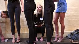 Seorang model duduk menunggu berparade selama casting untuk Melbourne Fashion Week, Australia (24/7/2019). Melbourne Fashion Week akan berlangsung 28 Agustus hingga 5 September 2019. (AFP Photo/William West)