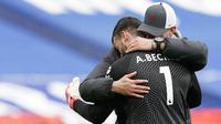 Kiper Liverpool, Alisson Becker, dipeluk oleh Jurgen Klopp usai laga melawan West Bromwich Albion pada laga Liga Inggris di Stadion the Hawthorns, Minggu (16/5/2021). Liverpool menang dengan skor 2-1. (Tim Keeton/Pool via AP)