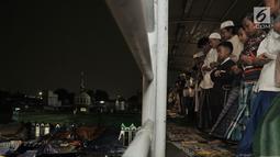 Sejumlah warga melaksanakan salat tarawih di atas Jembatan Penyebrangan Orang (JPO) Mushola Mifhtaul Jannah di Kawasan Pasar Gembrong, Jakarta, 5 Mei 2019. JPO yang biasa digunakan untuk akses menyeberang mendadak jadi area ibadah salat tarawih pada Ramadan 1440 H. (merdeka.com/Iqbal S. Nugroho)