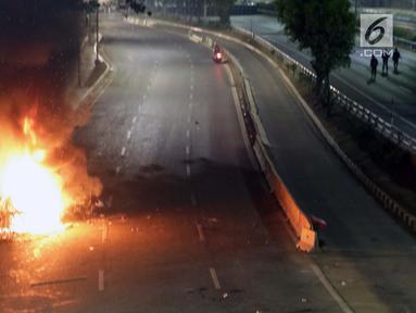 Api menyala membakar salah satu unit kendaraan kawat berduri milik aparat kepolisian di Jalan Gatot Subroto, Jakarta, Rabu (29/9/2019). Massa yang rata-rata berseragam sekolah dan pramuka bentrok dengan petugas sehingga jalan depan Kompleks Parlemen lumpuh. (Liputan6.com/HelmiFithriansyah)