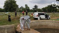 Petugas membawa peti jenazah yang akan dimakamkan dengan protokol COVID-19 di area khusus TPU Srengseng Sawah, Jakarta, Kamis (14/1/2021). TPU Srengseng Sawah mulai menerima pemakaman jenazah dengan protokol COVID-19 sejak Selasa (12/1) lalu. (Liputan6.com/Helmi Fithriansyah)