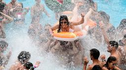 Seorang wanita menaiki ban karet saat berjoget di kolam renang selama Arenal Sound Music Festival 2019 di Burriana, Spanyol (31/7/2019). Festival musik ini berlangsung dari 30 Juli sampai 4 Agustus 2019.  (AFP Photo/Jose Jordan)