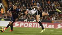 Bek Barcelona,, Jordi Alba, berebut bola dengan bek Valencia, Gbariel, pada laga La Liga Spanyol di Stadion Mestalla, Valencia, Minggu (26/11/2017). Kedua klub bermain imbang 1-1. (AFP/Jose Jordan)
