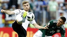 Striker Jerman, Timo Werner, berusaha melewati gelandang Meksiko, Edson Alvarez, pada laga Grup F Piala Dunia di Stadion Luzhniki, Moskow, Minggu (17/6/2018). Meksiko menang 1-0 atas Jerman. (AP/Antonio Calanni)