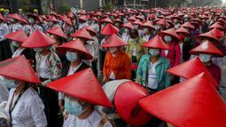 Barisan guru sekolah antikudeta yang mengenakan seragam dan topi tradisional Myanmar saat berpartisipasi dalam demonstrasi di Mandalay, Myanmar, Rabu (3/3/2021). Demonstran di Myanmar turun ke jalan lagi pada hari Rabu untuk memprotes perebutan kekuasaan bulan lalu oleh militer. (AP Photo)