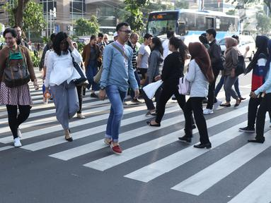 Warga melintasi Pelican Crossing di sekitar Halte Transjakarta Gelora Bung Karno, Jakarta, Jumat, (30/11). Penyeberangan pelican crossing diberlakukan selama revitalisasi jembatan penyeberangan orang (JPO) berlangsung. (Liputan6.com/Helmi Fithriansyah)