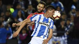 Bek Real Madrid, Nacho Fernandez, duel udara dengan striker Leganes, Guido Carrillo, pada laga La Liga di Stadion Municipal Butarque, Senin (15/4). Kedua tim bermain imbang 1-1. (AFP/Pierre Philippe Marcou)