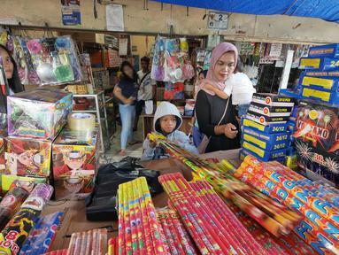 Pembeli saat memilih petasan di pasar gembrong, Jakarta, Senin (11/6). Imbas meledakanya pabrik petasan di tanggerang beberapa waktu lalu, harga petasan dan kembang api naik saat menjelang Lebaran 2018. (Liputan6.com/Herman Zakharia)