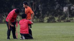 Staf pelatih Persija Jakarta memeriksa kaki Evan Dimas saat latihan di Lapangan Sutasoma, Jakarta, Rabu(28/1/2020). Gelandang Timnas Indonesia ini menjalani latihan terpisah karena masih pemulihan cedera. (Bola.com/M Iqbal Ichsan)