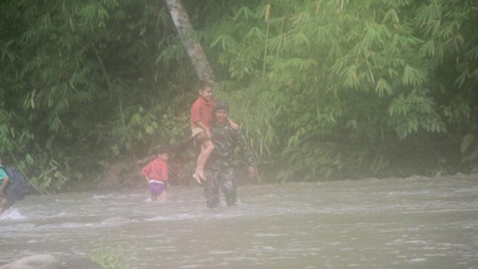 Sungai Sengkayam terletak di Kecamatan Entikong, Kabupaten Sanggau. Untuk menuju desa seberang, tidak ada akses jembatan. Saban hari anak-anak menyeberangi sungai untuk menuju SDN 16 Gun Jemak. (dok. TNI AD)