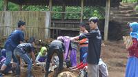Isrodin mendampingi siswa MTs Pakis, Cilongok, Banyumas untuk membuat media pendederan bibit tanaman. (Foto: Liputan6.com/Muhamad Ridlo)