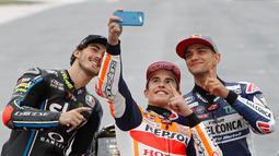 Juara Dunia MotoGP Marc Marquez (tengah) berswafoto bersama Juara Dunia Moto2 Francesco Bagnaia (kiri) dan Juara Dunia Moto3 Jorge Martin (kanan) usai Grand Prix Valencia di sirkuit Ricardo Tormo, Cheste, Spanyol, Minggu (18/11). (AP Photo/Alberto Saiz)