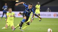 Penyerang Inter Milan, Lautaro Martinez membawa bola dari kawalan pemain Getafe, Djene Dakonam pada pertandingan babak 16 besar Liga Europa di Veltins-Arena di Gelsenkirchen, Jerman, Rabu, (5/8/2020). Inter menang 2-0 atas Getafe dan melaju ke perempat final.  (AP Photo/Ina Fassbender)