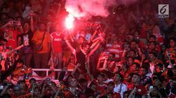 Suporter tim Macan Kemayoran menyalakan flare merayakan gelar juara Go-Jek Liga 1 Indonesia 2018 bersama Bukalapak yang diraih Persija di Stadion GBK, Jakarta, Minggu (9/12). Persija meraih gelar juara dengan 62 poin. (Liputan6.com/Helmi Fithriansyah)
