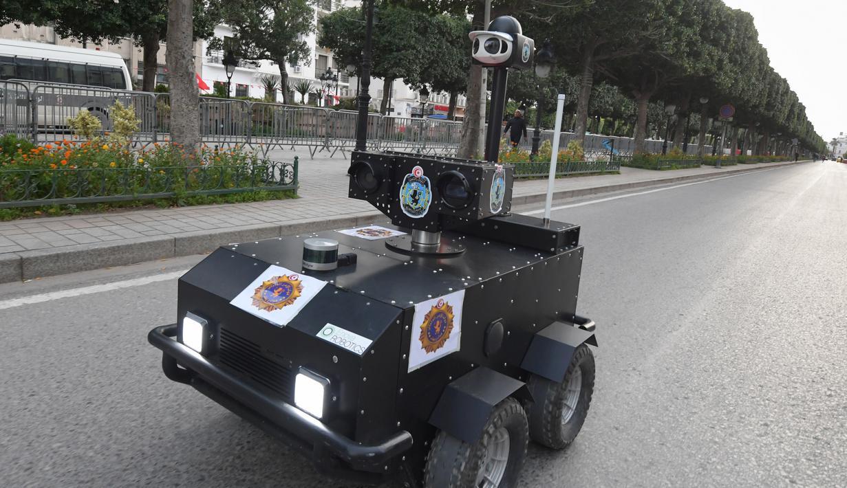 Robot polisi Tunisia berpatroli selama kebijakan penguncian (lockdown) di sepanjang Avenue Habib Bourguiba, pusat ibu kota Tunis, Rabu (1/4/2020). Robot itu dikendalikan dari jarak jauh untuk berkeliling dan membagikan sanksi terhadap warga yang melanggar aturan karantina. (FETHI BELAID/AFP)