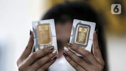 Pramuniaga menunjukkan emas batangan PT Aneka Tambang (Antam) Tbk di sebuah gerai emas, Jakarta, Senin (18/1/2021). Pada hari ini, harga emas Antam turun menjadi Rp 944 ribu per gram. (Liputan6.com/Johan Tallo)
