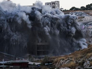 Sebuah bangunan Palestina yang sedang dibangun dihancurkan di desa Palestina Sur Baher di Yerusalem Timur (22/7/2019). Israel kembali menghancurkan sejumlah rumah Palestina yang dianggapnya dibangun secara ilegal di selatan Yerusalem. (AFP Photo/Ahmad Gharabli)