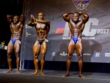 Para binaragawan berpose memamerkan ototnya dalam kompetisi binaraga di Port-au-Prince, Haiti, Minggu (23/7). Kompetisi ini diikuti oleh binaragawan antar dua negara, yaitu Haiti dan Republik Dominika. (AP/Dieu Nalio Chery)