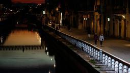Beberapa orang berjalan di Kanal Naviglio Grande, Milan, Italia, Selasa (10/3/2020). Sepinya salah satu tempat favorit bagi kehidupan malam tersebut imbas dari penerapan aturan lockdown yang diambil Italia demi mencegah penyebaran virus corona (COVID-19). (AP Photo/Antonio Calanni)