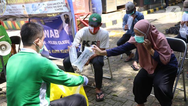 Warga memberikan kantong tes deteksi COVID-19 dengan metode GeNose C19 usai terjaring razia penggunaan masker di Kelurahan Sudimara Barat, Kota Tangerang, Kamis (27/5/2021). Tes tersebut untuk menekan penyebaran corona di wilayah tersebut. (Liputan6.com/Angga Yuniar)