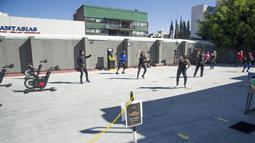 Sejumlah orang melakukan olahraga di luar ruangan di Mexico City pada 21 Januari 2021. Gimnasium di Mexico City beradaptasi dengan ruang terbuka dalam menghadapi lonjakan virus corona COVID-19. (Photo by CLAUDIO CRUZ / AFP)