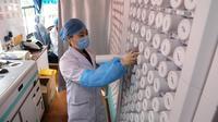 Petugas medis mengambil obat-obatan di sebuah rumah sakit keliling di Distrik Chang'an, Provinsi Hebei, 12 Maret 2020. Sebuah rumah sakit pengobatan tradisional China keliling menyediakan layanan kesehatan bagi penduduk setempat di tengah perang melawan virus corona COVID-19. (Xinhua/Liang Zidong)
