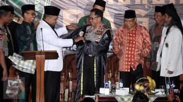 Sekjen Pagar Nusa M Nabil Haroen memberikan jubah kehormatan pencak silat Nahdlatul Ulama (PSNU) Pagar Nusa kepada Kapolri Jendral Tito Karnavian pada acara pembukaan Kongres III PSNU di TMII, Jakarta, Rabu (3/5). (Liputan6.com/Johan Tallo)