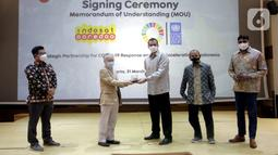 Resident Representative UNDP Indonesia, Norimasa Shimomura (kedua kiri) dan Presdir & CEO Indosat Ooredoo, Ahmad Al-Neama (tengah) bertukar cindermata usai menandatangani MoU penanggulangan pandemi COVID-19 dan percepatan pencapaian SDGs, di Jakarta, Rabu (31/3/2021). (Liputan6.com/Pool/Indosat)