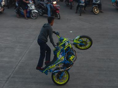 Seorang bikers melakukan aksi freestyle dengan motor di kawasan Kanal Banjir Timur, Jakarta, Selasa (29/5).Sekelompok pemuda di kawasan itu memanfaatkan waktu menunggu berbuka dengan melakukan atraksi freestyle yang mendebarkan. (Merdeka.com/Imam Buhori)