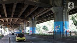 Mural bertema Covid-19 menghiasi pilar Jalan Tol Ir. Wiyoto Wiyono di kawasan Cempaka Putih, Jakarta, Rabu (2/12/2020). Mural tersebut juga bertujuan mengingatkan masyarakat akan bahaya Covid-19 yang masih terjadi hingga saat ini.  (Liputan6.com/Immanuel Antonius)