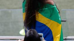 Fans wanita berpose dengan bendera Brasil sebelum pertandingan antara Brasil melawan Argentina pada semifinal Copa America 2019 di Stadion Mineirao, Brasil (2/7/2019). Di pertandingan ini Brasil menang 2-0 atas Argentina berkat gol striker Gabriel Jesus dan Roberto Firmino. (AP Photo/Nelson Antoine)