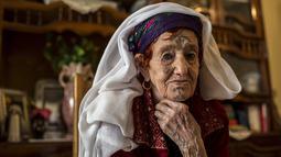 Wanita tua dari Chaouia pegunungan Aures, Aljazair tampak bertato dibagian mukanya. Untuk menebus dosanya karena menato tubuhnya wanita - wanita ini membayar denda dengan menyumbangkan harta mereka. (Dailymail.co.uk)