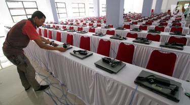 Teknisi menginstal laptop untuk tes calon pegawai negeri sipil (CPNS) di GOR Kelapa Gading, Jakarta Utara, Jumat (26/10). Tempat ini akan menjadi lokasi tes CPNS yang akan dilangsungkan pada Sabtu, 26 Oktober 2018. (Liputan6.com/JohanTallo)